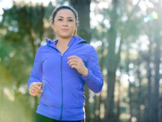 Female fitness model jogging through woodland
