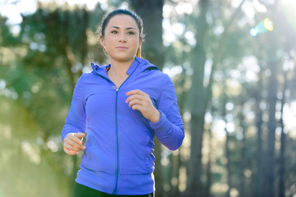 Female fitness model jogging through woodland