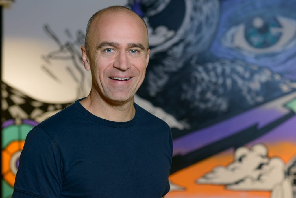 Contemporary corporate headshot of professional man in front of contemporary artwork