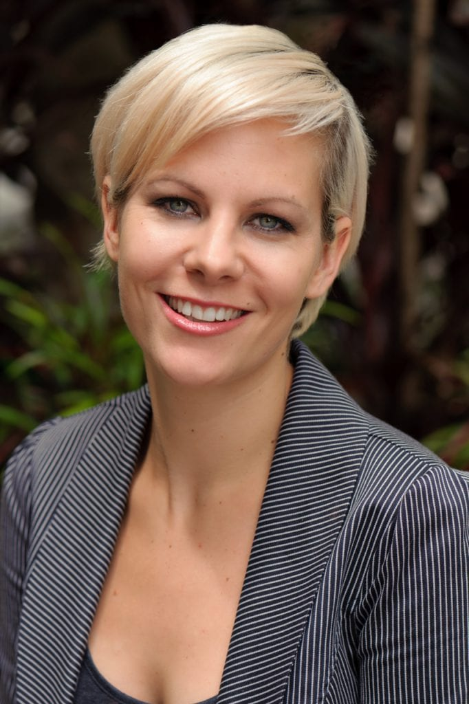 Contemporary corporate headshot of professional woman in front of greenery