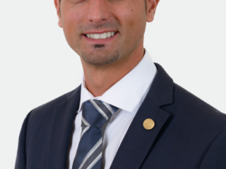 Corporate headshot of a man wearing a suit against a plain background
