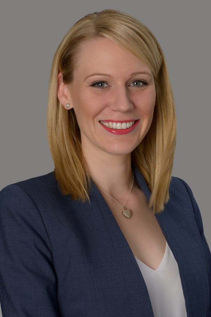 Corporate headshot of a smiling professional woman on a plain background