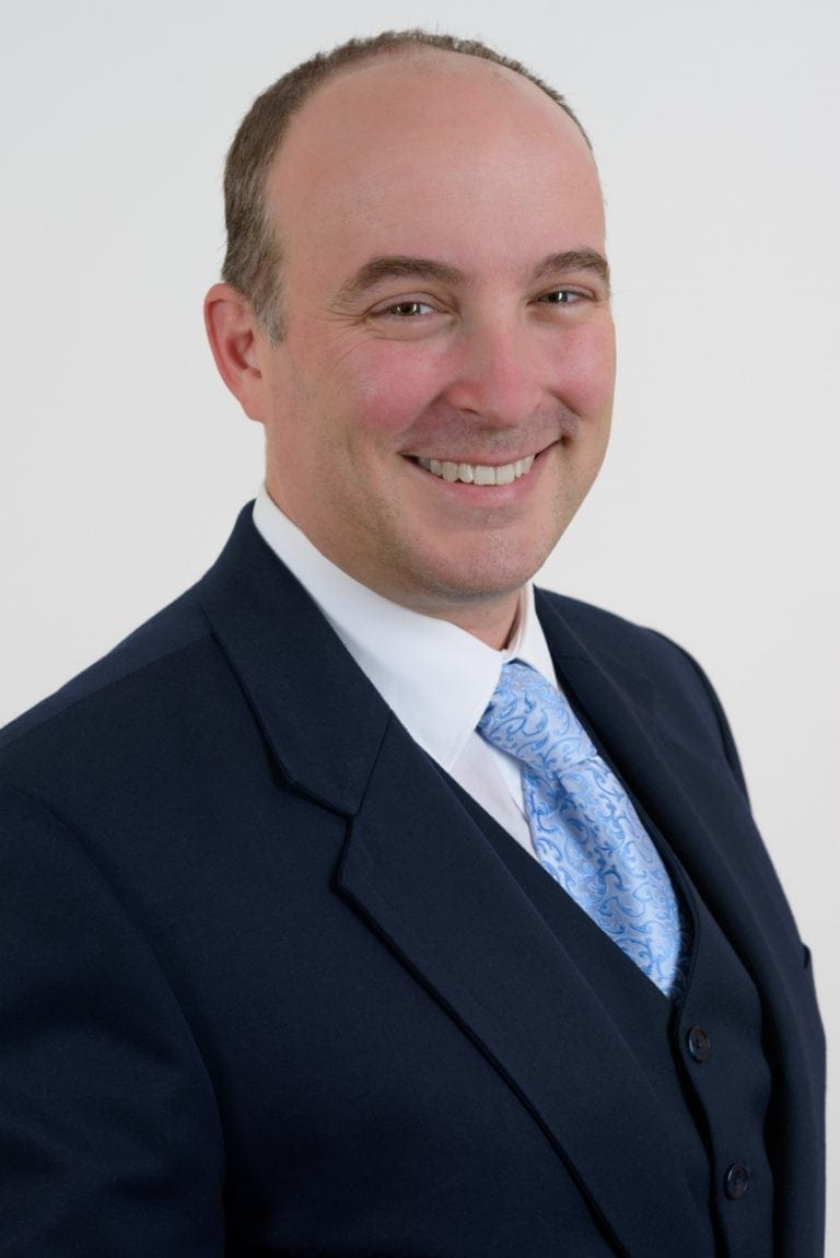Corporate headshot of a smiling lawyer on a plain background