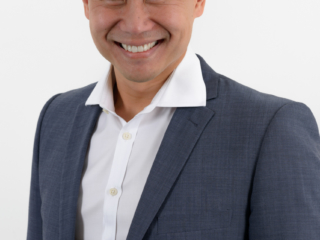Corporate headshot of a smiling man in open neck shirt and jacket on a plain background