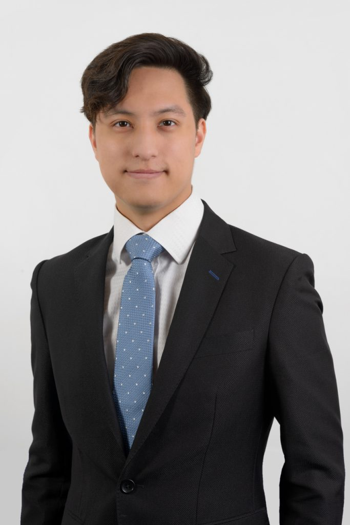 Corporate headshot of a young professional male on a plain background