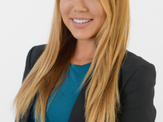 Corporate headshot of a young professional female on a plain background