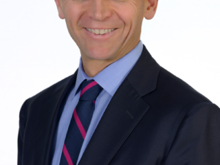 Corporate headshot of a smiling professional man on a plain background
