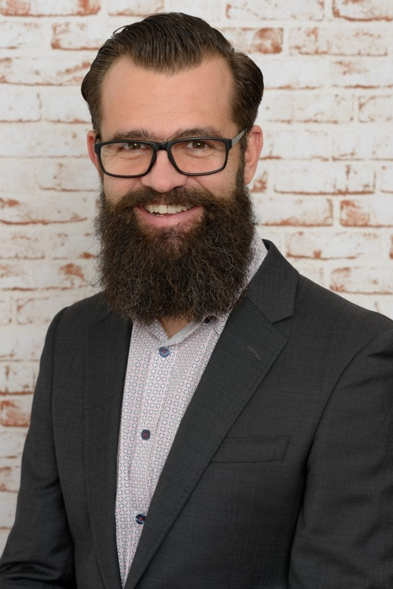 Corporate headshot of a smiling professional male against a brick wall