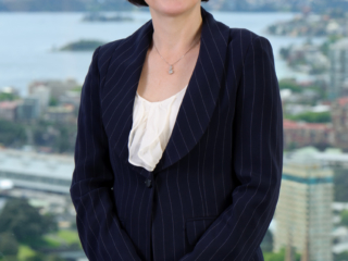 Executive portrait of female professional in front of window overlooking Sydney Harbour