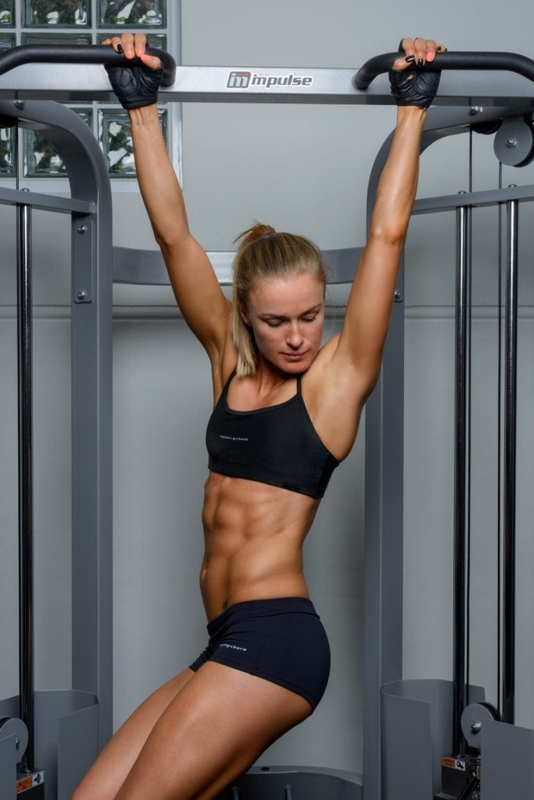 Female fitness model performing hanging crunches