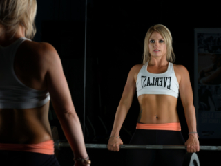 Female fitness model holding barbell looking in mirror at gym