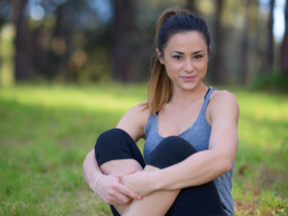 Fitness fashion model wearing leggings and vest top sitting in park