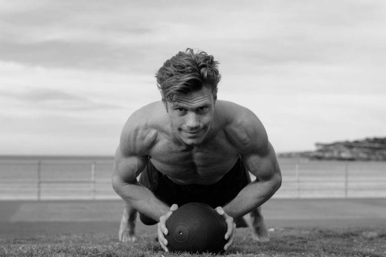 Fitness model doing pushup on medicine ball in beachside park