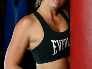 Female fitness model in sports bra next to punchbag in gym