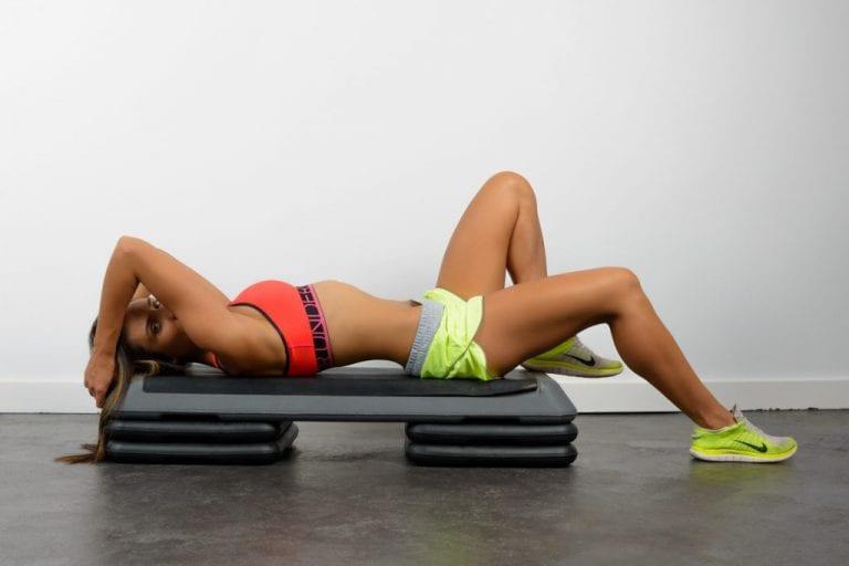 Female fitness model lies back on step