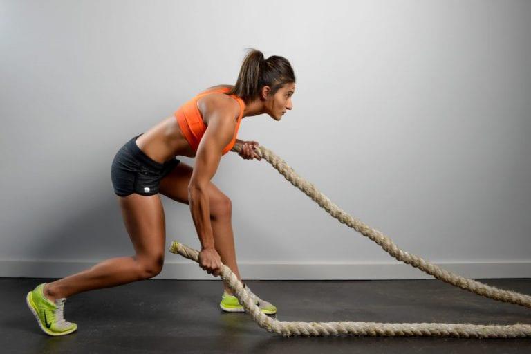 Female fitness model undertaking battle rope exercise