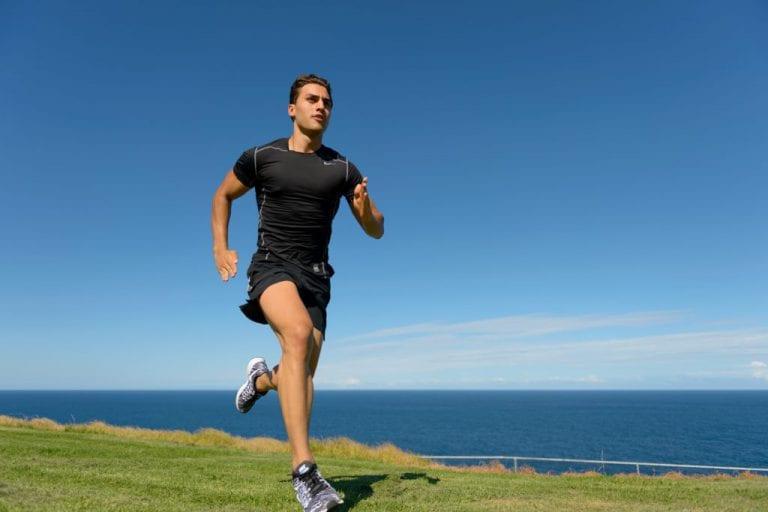 Fitness model running on clifftop park overlooking ocean