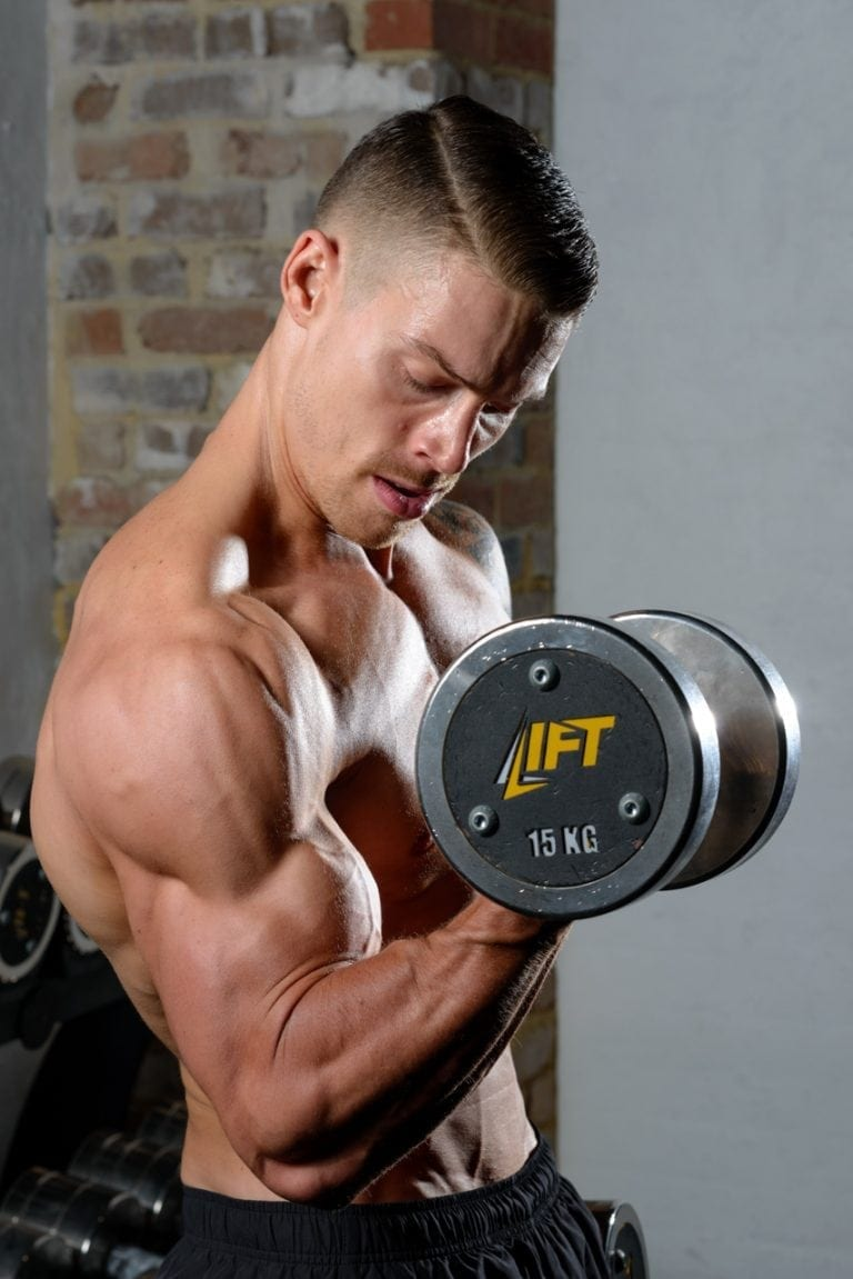Muscular male fitness model performs bicep curl in gym