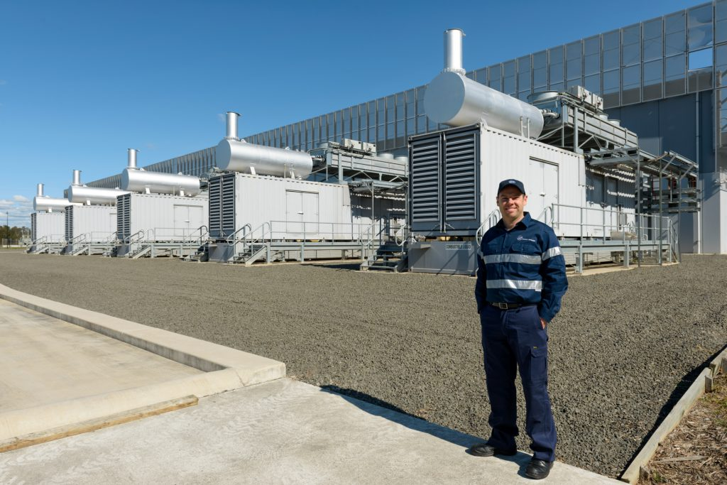 Engineer poses in front of infrastructure at industrial site